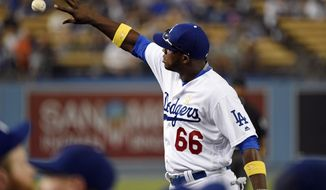 Los Angeles Dodgers' Yasiel Puig tosses a baseball to a fan during the first inning of a baseball game against the San Diego Padres in Los Angeles, Friday, Sept. 2, 2016. (AP Photo/Kelvin Kuo)
