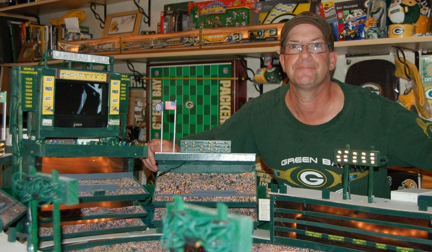 Ron Tanner poses in this photo taken on Wednesday, Sept. 6, 2016, with his model of Lambeau Field, created from wood, cardboard, string lights and more. Tanner, of Beloit, Wis., said the model took five years to build.  (Zac Bellman/Beloit Daily News via AP)