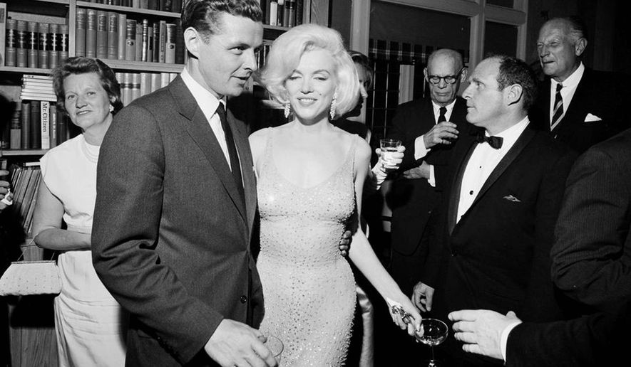 "In this May 19, 1962, photo provided by the John F. Kennedy Presidential Library and Museum, actress Marilyn Monroe wears the iconic gown that she wore while singing ""Happy Birthday"" to President John F. Kennedy at Madison Square Garden, during a reception in New York City. Standing next to Monroe is Steve Smith, President Kennedy's brother-in-law. Julien's Auctions will offer Monroe's gown at auction in Los Angeles on Nov. 17, 2016. (Cecil Stoughton/White House Photographs, John F. Kennedy Presidential Library and Museum via AP)"