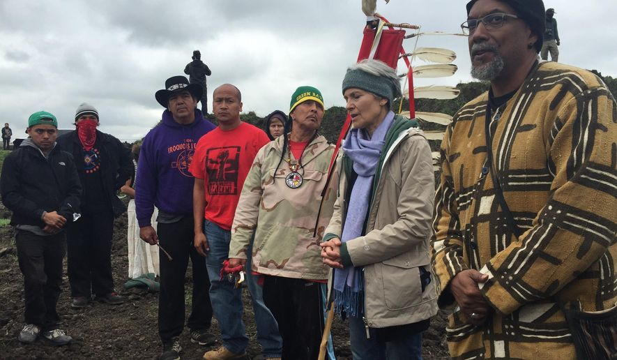 In this photo provided by LaDonna Allard, Green Party presidential candidate Jill Stein, second from right, participates in an oil pipeline protest, Tuesday, Sept. 6, 2016 in Morton County, N.D. North Dakota authorities plan to pursue charges against Green Party presidential candidate Jill Stein for spray-painting construction equipment at a Dakota Access Pipeline protest. Morton County Sheriff Kyle Kirchmeier said Tuesday that the charges would be for trespassing and vandalism. (LaDonna Allard via AP)