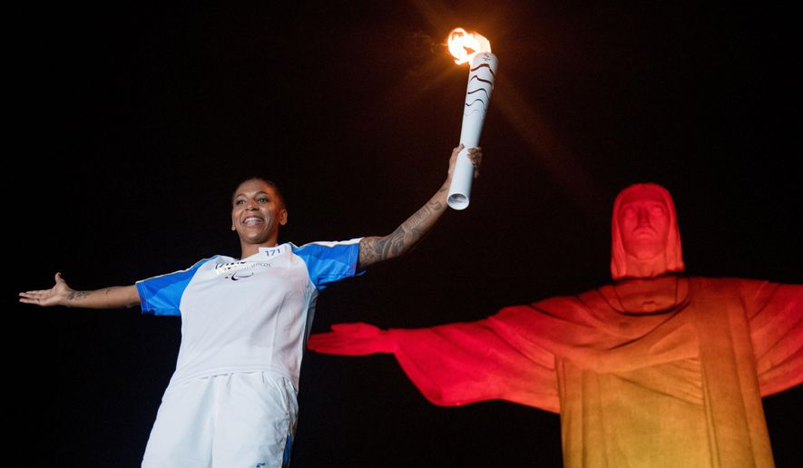 Brazilian judo gold medalist Rafaela Silva carries the Paralympic torch in front of the Christ the Redeemer statue on its way for the opening ceremony in Rio de Janeiro, Brazil, Tuesday, Sept. 6, 2016. (AP Photo/Mauro Pimentel)
