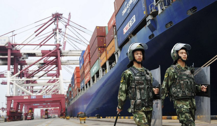 China's paramilitary police patrol as containers are loaded on to a cargo ship for export at a port in Qingdao in east China's Shandong province on Sept. 8, 2016. China's exports rose in August for the first time in two years, while the contraction in imports narrowed in a positive sign for global economic growth. (Chinatopix via AP)