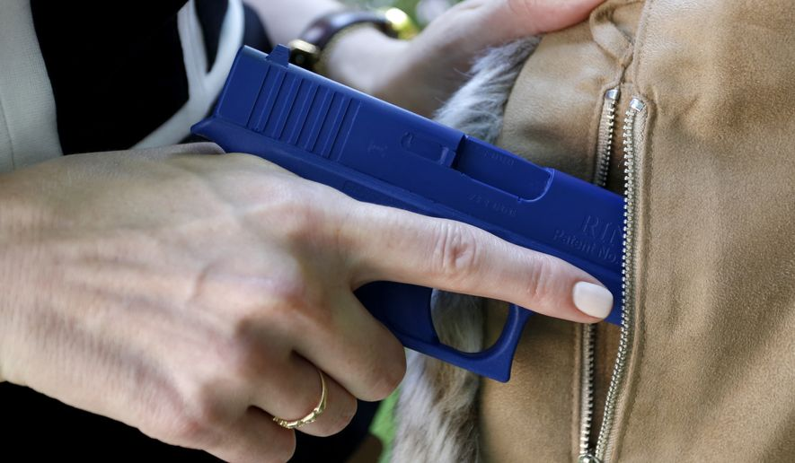 In this Aug. 29, 2016 file photo, Marilyn Smolenski uses a mock gun to demonstrate how to pull a handgun out of the concealed carry clothing she designs at her home in Park Ridge, Ill.  (AP Photo/Tae-Gyun Kim) **FILE**