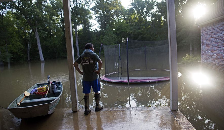 David Key looks at the back yard of his flooded home in Prairieville, La., Tuesday, Aug. 16, 2016. Key, an insurance adjuster, fled his home as the flood water was rising with his wife and three children and returned today to assess the damage. (AP Photo/Max Becherer)