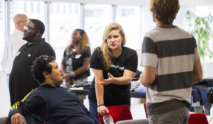 Cheri Garcia, center, talks to Shawn Shinohara, left, and Teddy Hays, right, during a Cornbread Hustle event on Aug. 16, 2016 in Dallas. Cornbread Hustle is a staffing agency that places released convicts.   (Ashley Landis/The Dallas Morning News via AP)