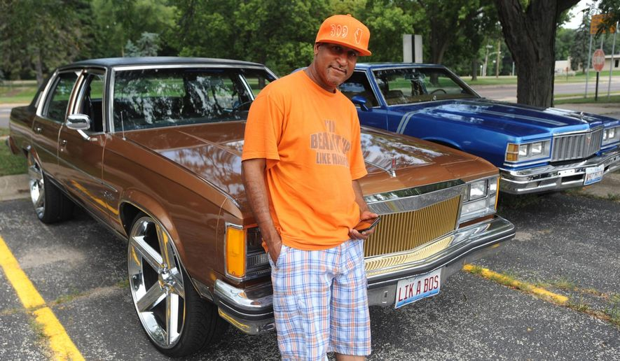 ADVANCE FOR USE SATURDAY, SEPT. 10, 2016 AND THEREAFTER - In this  July 30, 2016 photo, Jermaine Hickman stands with his 1979 Oldsmobile Ninety-Eight with 26-inch rims during a gathering of the members of the Flossin Car Club in Peoria, Ill. The club, known for its auto's extra large rims and flashy paint jobs, was started about a year ago by Hickman and has gained a huge following via social media. (Matt Dayhoff/Journal Star via AP)
