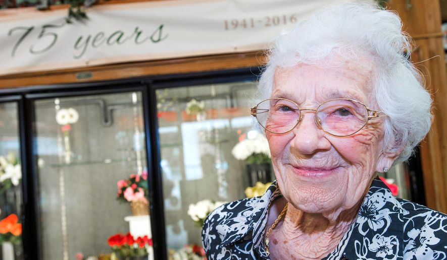 ADVANCE FOR USE SUNDAY, SEPT. 11, 2016 AND THEREAFTER - In this Aug.  9, 2016 photo, Campus Florist owner Anne Johnston smiles in her store in Champaign, Ill. The flower shop in the heart of the University of Illinois' business district, and Johnston, its sole owner, are marking a unique milestone this year, three quarters of a century in business. (Robin Scholz/The News-Gazette via AP )