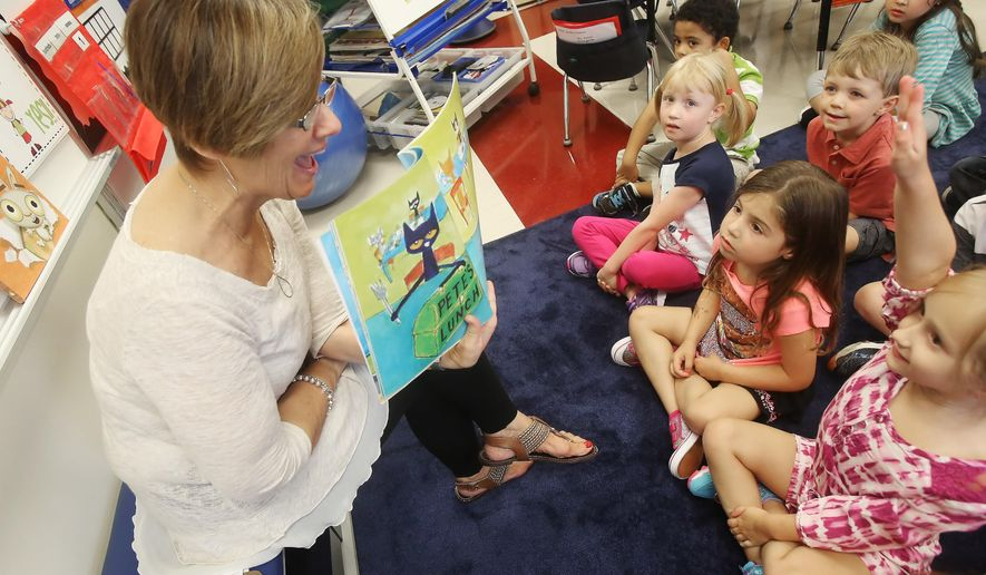 ADVANCE FOR USE SATURDAY, SEPT. 10, 2016 AND THEREAFTER - In this  Aug. 17, 2016 photo, teacher Mimi Batson reads a story in kindergarten class on the first day of class at Hawthorn Townline Elementary School in Vernon Hills, Ill. Though kindergarten remains optional in Illinois, full-day sessions are increasingly the norm in the suburbs, gaining favor with parents and educators alike. (Gilbert R. Boucher/Daily Herald via AP)