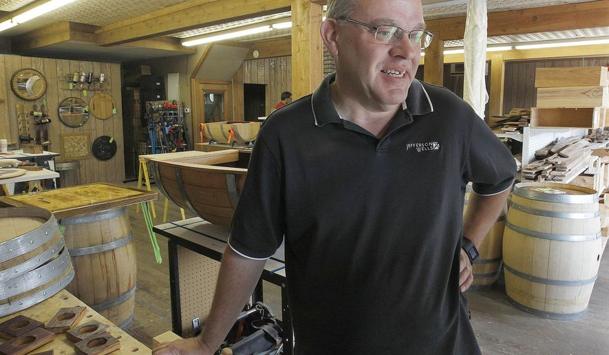 ADVANCE FOR USE SUNDAY, SEPT. 11, 2016 AND THEREAFTER - In this Aug.  17, 2016 photo, Dave Chaput, owner of Live Oak Wine Decor stands in his workshop in Millstadt, Ill. He always loved woodworking, and turned his hobby into a business after his retirement. Live Oak Wine Decor is what it sounds like: Chaput takes used wine barrels and wooden shipping crates and makes them into decorative and functional items. (Tim Vizer/Belleville News-Democrat, via AP)