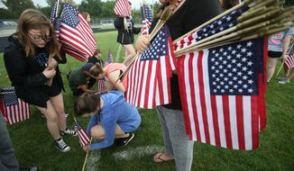 Students at Civic Memorial High School in Bethalto, Ill., push some of the 2,996 American flags into the football field Thursday, Sept. 8, 2016, for a Sept. 11 Memorial Ceremony in remembrance of the 15th anniversary of the terrorist attacks on America. Each flag represents one of the people who died in the attack. (John Badman/The Telegraph via AP)
