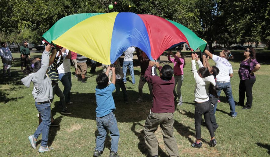 FILE - In this July 26, 2012 file photo children and adults uses a play parachute as part of an exercise activity during a wellness program run jointly by the La Familia Counseling Center INC., and the YMCA in Sacramento, Calif. Voters approved Proposition 63 in 2004 to provide funding for mental health services, but a California watchdog agency, the Little Hoover Commission, reported Thursday, Sept. 8, 2016, that 12 years after voters approved a 1 percent tax on millionaires, the state still can't readily show how the money is spent or who is helped. (AP Photo/Rich Pedroncelli, File)