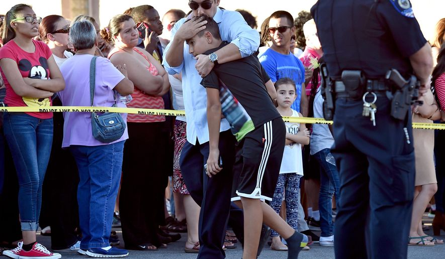 A parent hugs his child after being released from Walter Johnson Junior High School Wednesday, Sept. 7, 2016, in Las Vegas. Hundreds of anxious parents staked out a Las Vegas middle school after mercury was found and federal officials kept more than a thousand students for up to 17 hours to screen them for exposure to the neurotoxin.. (David Becker/Las Vegas Review-Journal via AP)