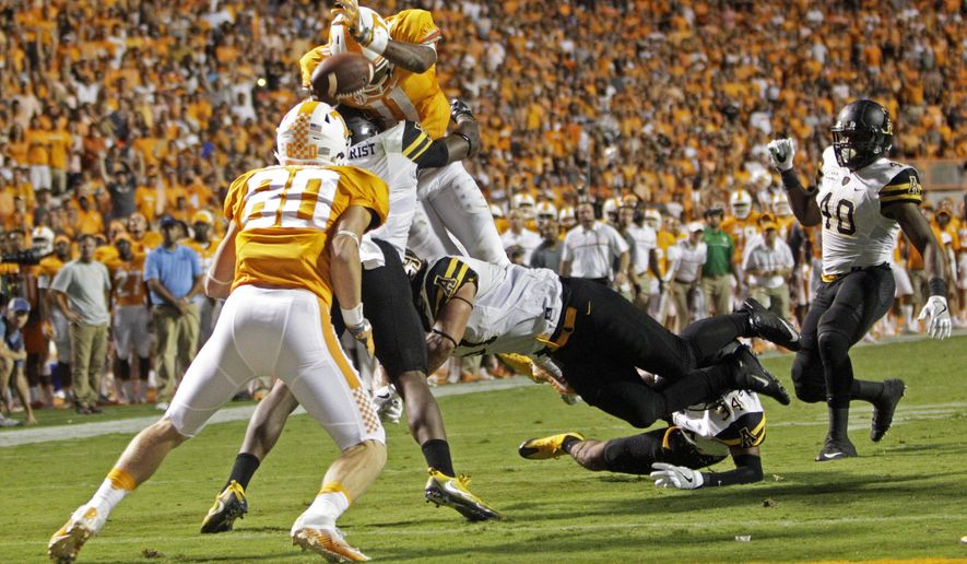 FILE -- In this Sept. 1, 2016 file photo, Tennessee quarterback Joshua Dobbs (11) leaps for the end zone as he's hit by Appalachian State linebacker Kennan Gilchrist (6), defensive lineman Caleb Fuller (51) and defensive back Desmond Franklin (34) during overtime of an NCAA college football game in Knoxville, Tenn. Dobbs fumbled; the ball was recovered by Jalen Hurd for a touchdown to give Tennessee a 20-13 win. Tennessee's offense is seeking more consistency and productivity heading into Saturday's game with Virginia Tech at Bristol Motor Speedway. (AP Photo/Wade Payne, File)
