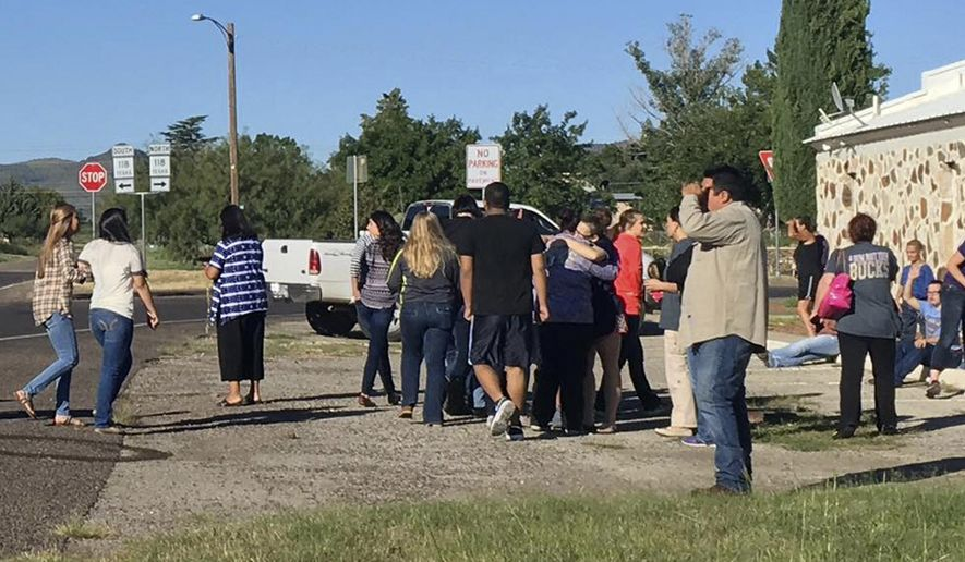 In this photo provided by the Alpine Avalanche, people gather near the Alpine High School school campus after a shooting, in Alpine, Texas, Thursday, Sept. 8, 2016. A student died of an apparent self-inflicted gunshot wound, the Brewster County sheriff said. (Gail Yovanovich/Alpine Avalanche via AP)