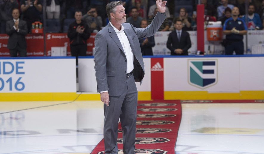 Former NHL player Patrick Roy waves to the applauding crowd before dropping the puck for a ceremonial face-off as Team Europe and Team North America play an exhibition game at the World Cup of Hockey, Thursday, Sept. 8, 2016, in Quebec City. (Jacques Boissinot/The Canadian Press via AP)