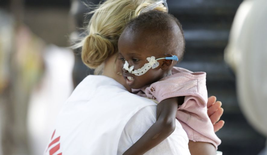 In this photo taken Monday Aug. 29, 2016. Jean Stowell, an American midwife, from Loconia, New Hampshire, who is in charge of an emergency feeding center, carries 18-month-old Yakubu a malnourished child at the center run by Doctors Without Borders in Maiduguri, Nigeria. The whimpers from skeletally thin babies too weak to cry out are a harbinger of worse things to come: A quarter of the kids lucky enough to make it to this emergency feeding center are dying, the latest victims of Boko Haram's Islamic insurgency. (AP Photo/Sunday Alamba)