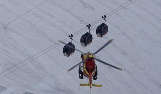 An EC-135 helicopter operated by the French Societe' Civile hovers, Friday, Sept. 9, 2016, near three cars of the Panoramic Mont Blanc cable car that stalled around 4 p.m. (1400 GMT) on Thursday, after its cables reportedly tangled. (AP Photo/Luca Bruno)