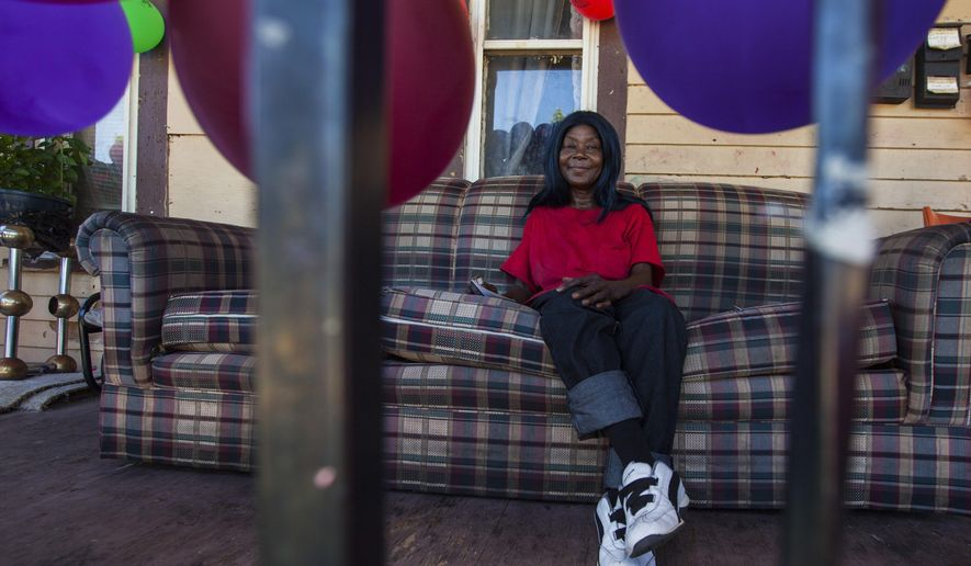 ADVANCE FOR USE FOR USE SUNDAY, SEPT. 11, 2016 AND THEREAFTER - In this Aug. 1, 2016 photo, Linda Williams sits a couch on the porch of her home in Saginaw, Mich. Williams has been blowing balloons up by hand and arranging them on her porch for years. (Josie Norris/The Saginaw News/MLive.com via AP)