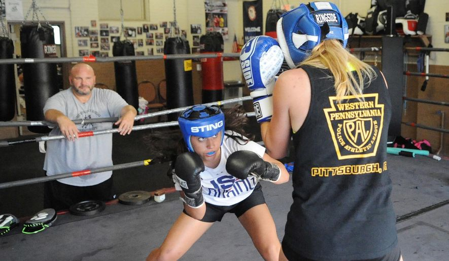 In this July 25, 2016 photo, Allyanna Bates, of Upper St. Clair, and Jordyn Helger, from Fox Chapel, practice sparring at the Pittsburgh Boxing Club in the Brookline neighborhood, of Pittsburgh, while their coach John Brunick watches. (Gracey Evans/Pittsburgh Post-Gazette via AP)