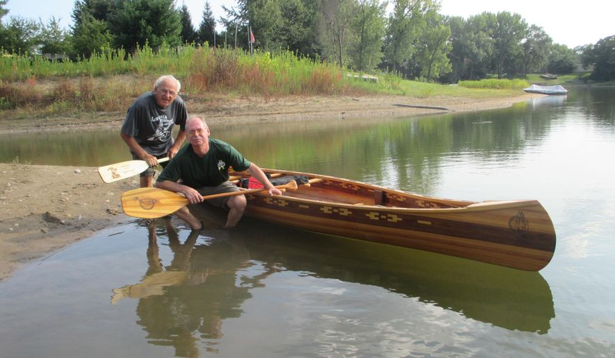 In this Aug. 8, 2016 photo, David Hupke and his father, Horst Hupke, pose with the canoe they built over a period of nine months near their home in Pekin, Ill. The handcrafted canoe may have been what saved David's life. As  a young man a wooden canoe caught his attention. It was one that he wanted to build with his dad, someday. Life got in the way and the plan was delayed for decades. Then David got gravely ill In 1993. He was struck with an intestine disorder and a terminal diagnosis. David pulled through and building the canoe provided him with physical therapy he needed to recover. (Jeanette Brickner/The Pekin Times via AP)