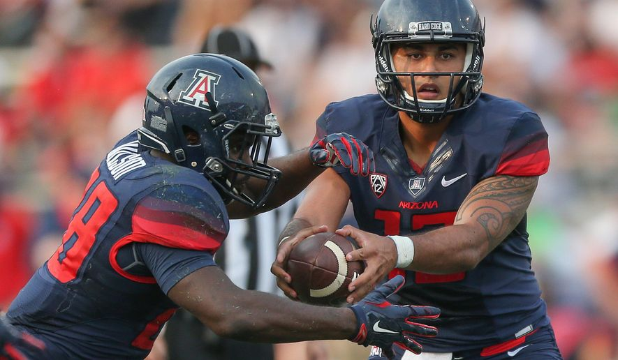 FILE - In this Sept. 12, 2015, file photo, Arizona quarterback Anu Solomon (12) fakes a handoff to running back Nick Wilson during an NCAA college football game against Nevada in Reno, Nev. Arizona host Grambling State on Saturday. (AP Photo/Cathleen Allison, File)