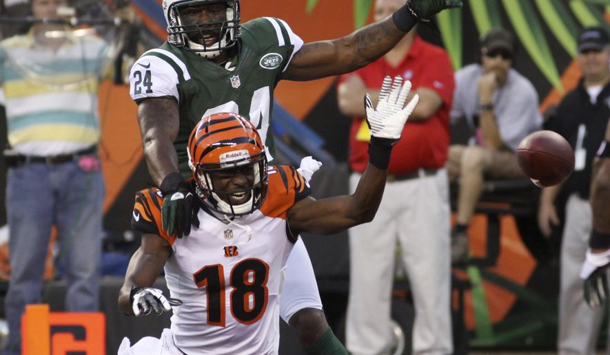 FILE - In this Aug. 10, 2012, file photo, New York Jets defensive back Darrelle Revis (24) knocks the ball loose from Cincinnati Bengals wide receiver A.J. Green  during the first half of an NFL preseason football game in Cincinnati. Green vs. Revis would appear to be one of the marquee matchups of Week 1 in the NFL. But the New York Jets might use multiple defenders against the Cincinnati Bengals star receiver on Sunday. (AP Photo/Tom Uhlman, File0
