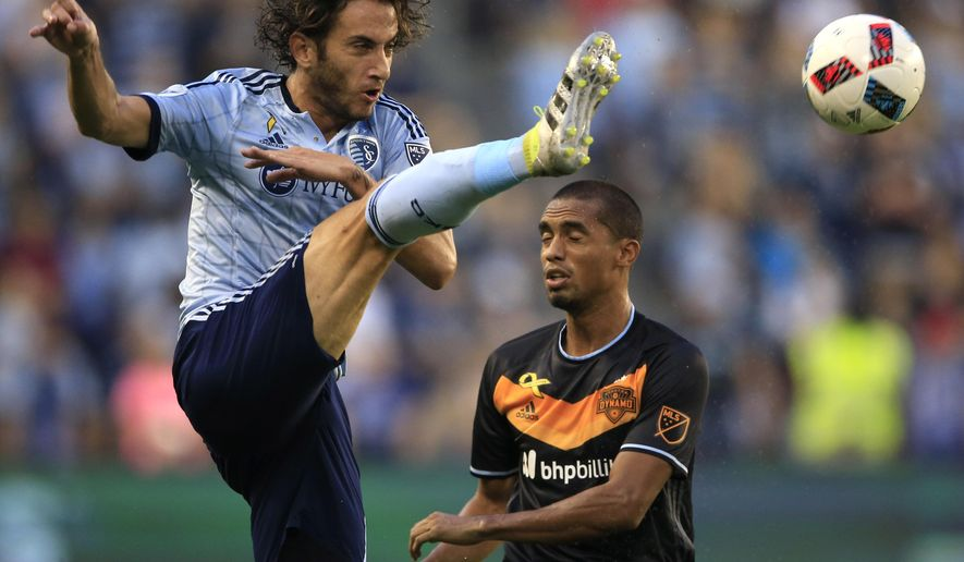 Sporting Kansas City defender Nuno Coelho, left, controls a pass next to Houston Dynamo forward Mauro Manotas during the first half of an MLS soccer match in Kansas City, Kan., Friday, Sept. 9, 2016. (AP Photo/Orlin Wagner)
