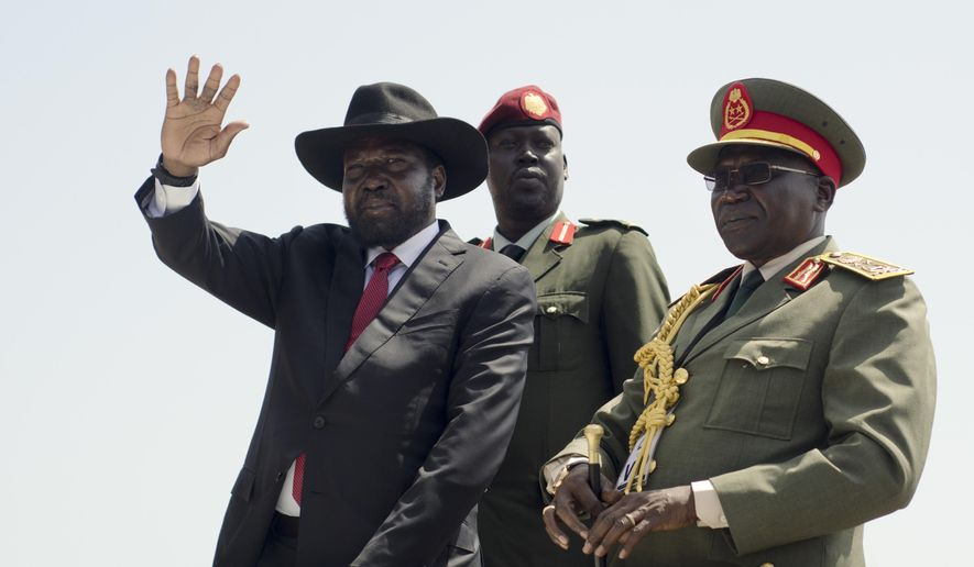 FILE - In this Thursday, July 9, 2015 file photo, South Sudan's President Salva Kiir, left, accompanied by army chief of staff Paul Malong, right, waves during an independence day ceremony in the capital Juba, South Sudan. A confidential U.N. report obtained by The Associated Press on Friday, Sept. 9, 2016 says South Sudan's deadly fighting in July was directed by the highest levels of government, and that leaders are intent on a military solution that worsens ethnic tensions. (AP Photo/Jason Patinkin, File)