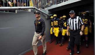 Michigan head coach Jim Harbaugh, left, leads his team out of the tunnel before an NCAA college football game against Central Florida at Michigan Stadium in Ann Arbor, Mich., Saturday, Sept. 10, 2016. Michigan won 51-14. (AP Photo/Tony Ding)
