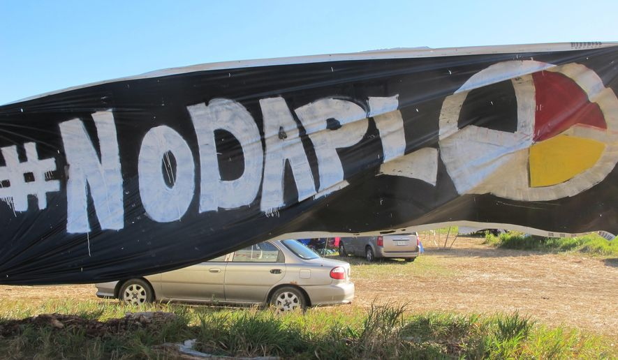 "A banner protesting the Dakota Access oil pipeline is displayed at an encampment near North Dakota's Standing Rock Sioux reservation on Friday, Sept. 9, 2016. The Standing Rock Sioux tribe's attempt to halt construction of an oil pipeline near its North Dakota reservation failed in federal court Friday, but three government agencies asked the pipeline company to ""voluntarily pause"" work on a segment that tribal officials say holds sacred artifacts. (AP Photo/James MacPherson)"