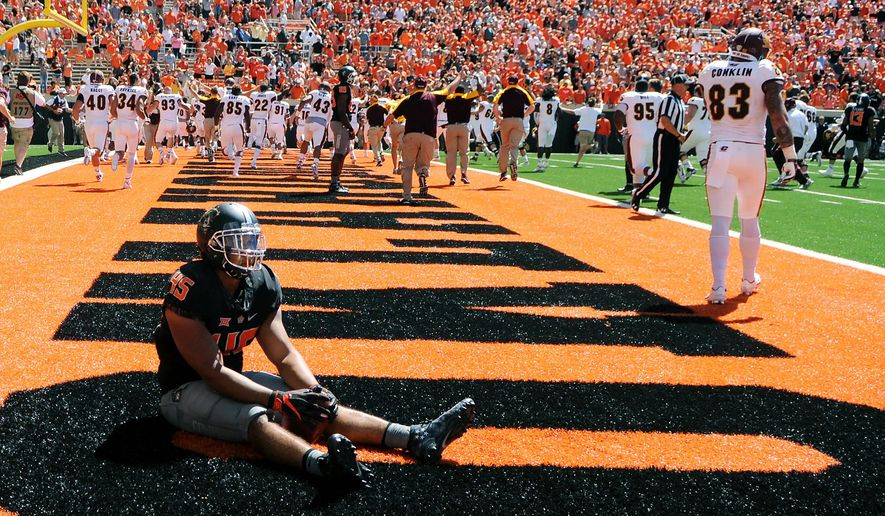 Oklahoma State linebacker Chad Whitener sits alone in the Central Michigan end zone while the Central Michigan team celebrates a last second touchdown by wide receiver Corey Willis, resulting in a 30-27 win over Oklahoma State following an NCAA college football game in Stillwater, Okla., Saturday, Sept. 10, 2016.(AP Photo/Brody Schmidt)