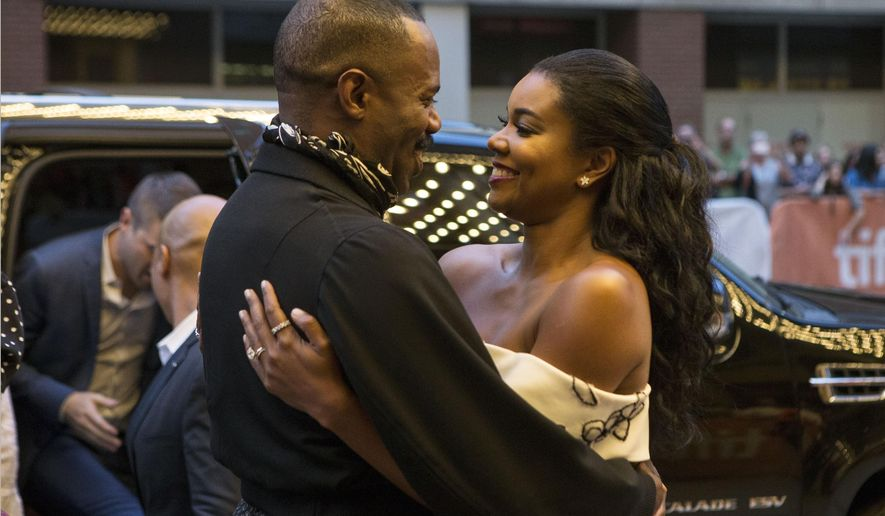 """Colman Domingo, left, embraces fellow actor Gabrielle Union as they arrive on the red carpet for the film """"Birth of a Nation"""" during the 2016 Toronto International Film Festival in Toronto on Friday, Sept. 9, 2016. (Chris Young/The Canadian Press via AP)"""