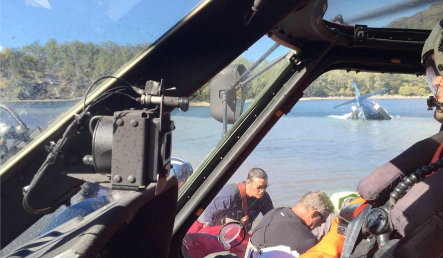 This photo provided by the U.S. Coast Guard shows a Coast Guard Air Station Kodiak MH-60 Jayhawk crew preparing to transport survivors of a plane crash near Uganik Lake on Kodiak Island, Alaska, Sept. 9, 2016. The aircrew transported three people from a downed De Havilland DHC-2 float plane to awaiting emergency medical services personnel in Kodiak. (Petty Officer 1st Class William Colclough/U.S. Coast Guard via AP)