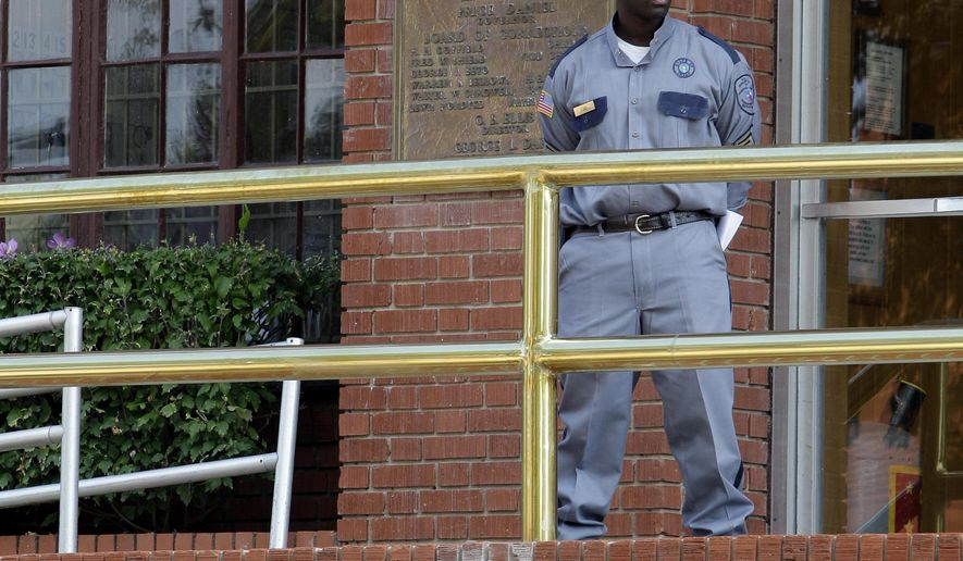 FILE - In this Sept. 21, 2011 file photo, a corrections officer keeps watch outside the Texas Department of Criminal Justice Huntsville Unit in Huntsville, Texas. Texas highest criminal court has become an unlikely source for a lull in executions this year in the nation's most active death penalty state. (AP Photo/David J. Phillip, File)