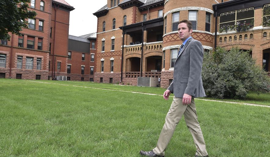 ADVANCE FOR WEEKEND EDITIONS SEPT 10-11 - In this Friday, Aug. 26, 2016 photo, Cory Turner, superintendent of the Cherokee Mental Health Institute walks across the institute's campus in Cherokee, Iowa. More than a year after two of Iowa's four mental health institutes shut down, the institute in Cherokee is operating similarly to how it had been in recent years. (Tim Hynds/Sioux City Journal via AP)