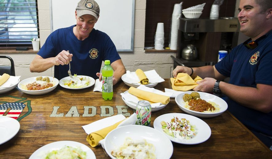 In this Monday, Sept. 5, 2016 photo, firefighters Robert Cheatham, left, and Andy Shockley enjoy lunch courtesy of a local Olive Garden restaurant in Knoxville, Tenn. Every year for the last decade and a half, Olive Garden restaurants around the country have delivered meals to first responders on Labor Day. For the last three years, Olive Garden No. 1092 has delivered a pasta to the fire station, less than a mile from the restaurant. (Caitie McMekin/Knoxville News Sentinel, via AP)