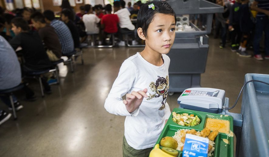 ADVANCE FOR WEEKEND EDITIONS SEPT. 10-11 - In this Tuesday, Aug. 30, 2016 photo, sixth-grader Pan Poe Si checks out of the lunch line at Meredith Middle School in Des Moines, Iowa. Des Moines schools are cooking lunches with immigrants in mind by incorporating different 'flavor profiles' for various ethnic backgrounds. Students represent Syria, Sudan, Nepal, Thailand, Burma, Mexico and Japan. (Rachel Mummey/The Des Moines Register via AP  )