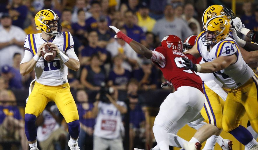 LSU quarterback Danny Etling (16) looks to pass as center William Clapp (64) blocks against Jacksonville State defensive end Eliah Goodman (91) in the first half of an NCAA college football game in Baton Rouge, La., Saturday, Sept. 10, 2016. (AP Photo/Gerald Herbert)