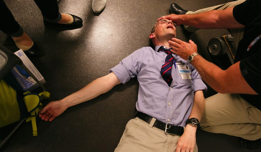 In this Monday, Aug. 22, 2016 photo, Dr. David Carlbom, of the Harborview Paramedic Training Program, on floor, poses as an unresponsive victim of an airway obstruction during the first-day session with new University of Washington medical students, in Seattle. He was assisting clinical educator Mike Helbock, of the UW School of Medicine.  (Erika Schultz/The Seattle Times via AP)