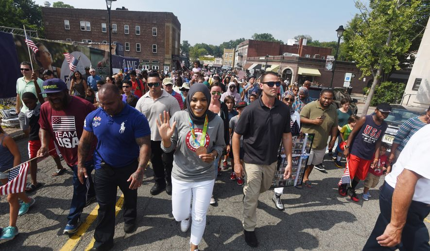 Ibtihaj Muhammad, center, who won a bronze medal in the women's team sabre event at Rio, marches in a parade held in her honor Saturday, Sept. 10, 2016, in Maplewood, N.J. She was the first U.S. athlete to compete while wearing a hijab. (Chris Pedota/The Record via AP)