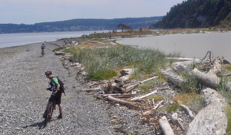 This July 12, 2014 photo shows cyclists riding on Washington State Parks' Miller Peninsula Property  in Port Townsend,  Wash. Washington state boasts that his is one of the longest public beaches in the region.  (Tristan Baurick/Kitsap Sun via AP)