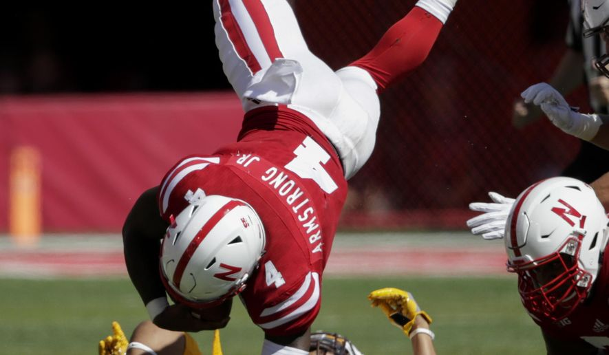 Nebraska quarterback Tommy Armstrong Jr. (4) is upended by Wyoming defensive back Marcus Epps, rear, during the first half of an NCAA college football game in Lincoln, Neb., Saturday, Sept. 10, 2016. (AP Photo/Nati Harnik)
