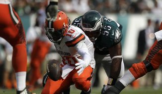 Cleveland Browns' Robert Griffin III grabs a loose ball against Philadelphia Eagles' Brandon Graham during the second half of an NFL football game, Sunday, Sept. 11, 2016, in Philadelphia. (AP Photo/Michael Perez)