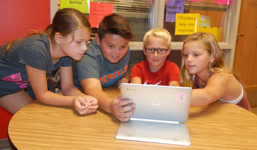 Oakland-Craig Elementary School students, from left,  Gabi Linder, Laughlin McNeill, Owen Anderson and Shea Johnson work on Chromebook on Aug. 31, 2016 in Oakland, Neb.  Oakland-Craig Public Schools has updated its technology in more than one way for the 2016-17 school year. This year, every senior has a MacBook, while all underclassmen in grades 9-11 have Chromebooks.  (Tammy Real-McKeighan/The Tribune via AP)