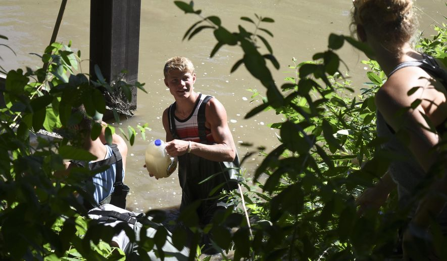 In this May 29, 2015 photo, Cody Nelson hands Payton Nelson a jug full of water from the Shell Creek near Newman Grove for use in tests to determine the creeks water quality in Newman Grove, Neb.   Since 1988, complaints of fish kills in the creek have attracted the attention of groups from the Lower Platte North Natural Resources District to law enforcement. The water pooled cloudy and pungent in some places, and streamed by with contaminants where it flowed. (Marcella Mercer /The Norfolk Daily News via AP)