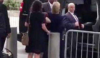 Hillary Clinton (center) leaving the 9/11 commemoration Sunday