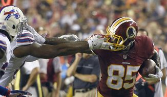 FILE - In this Aug. 26, 2016, file photo, Washington Redskins tight end Vernon Davis (85) tries to get past Buffalo Bills outside linebacker Randell Johnson, second from left, and Bills defensive back Jonathan Meeks, far left,  during the first half of an NFL preseason football game in Landover, Md. Jordan Reed's 11 touchdown season was a product of his breakout talent and the Redskins' tight end friendly offense that should be even better with Niles Paul back and Vernon Davis in the fold. (AP Photo/Nick Wass, File)