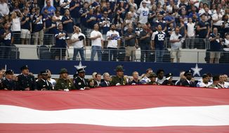 Former president George W. Bush and Laura Bush along with Dallas Cowboys head coach Jason Garrett, and first responders, stand of the national anthem prior to a NFL football game between the Dallas Cowboys and the New York Giants on Sunday, Sept. 11, 2016, in Arlington, Texas. (AP Photo/Michael Ainsworth)