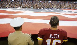 Washington Redskins quarterback Colt McCoy (16) joins a member of the US Marine Corps holding a giant US Flag before an NFL football game against the Pittsburgh Steelers in Landover, Md., Monday, Sept. 12, 2016. (AP Photo/Patrick Semansky)