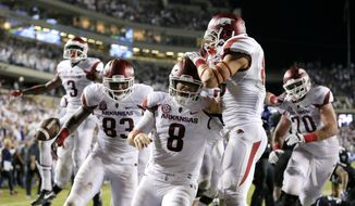 Arkansas quarterback Austin Allen (8) celebrates with Drew Morgan, center right, Dominique Reed (3), Jeremy Sprinkle (83) and Dan Skipper (70) after scoring a touchdown on a run in the second overtime against TCU in an NCAA college football game, Saturday, Sept. 10, 2016, in Fort Worth, Texas. Arkansas won 41-38. (AP Photo/Tony Gutierrez)